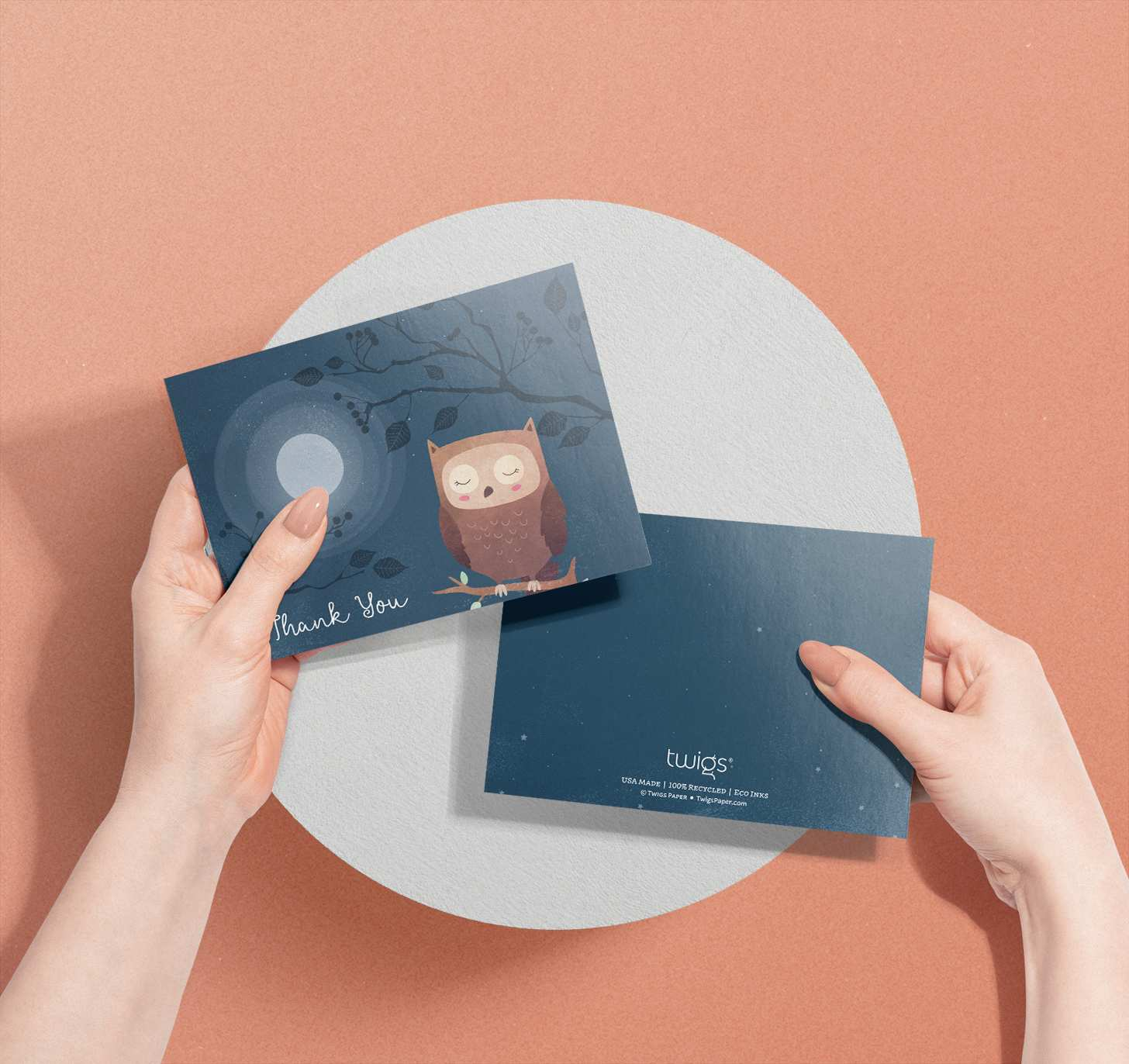 Woman's hands holding card with cute brown owl on dark blue nighttime design