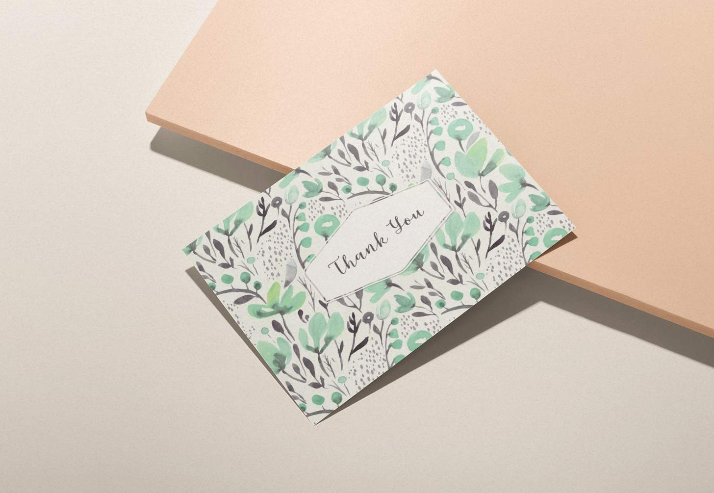 Green floral design thank you card on pink background