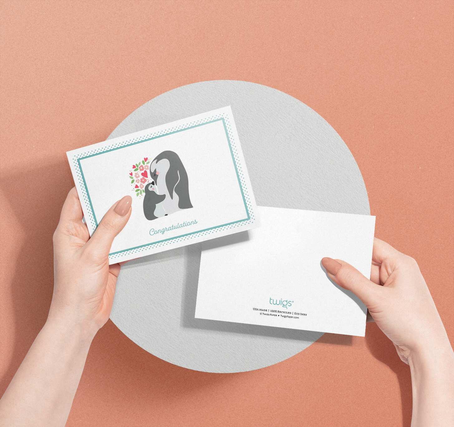 Woman's hands holding two cards with mother and baby penguin designs
