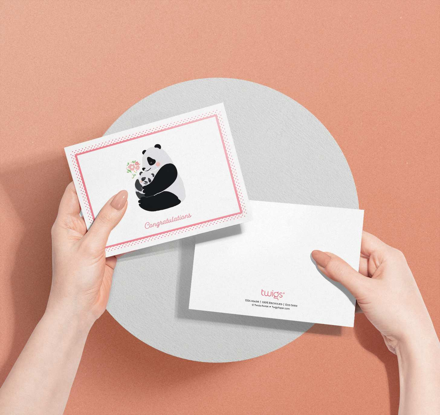 Woman's hands holding two cards with mother and baby panda designs