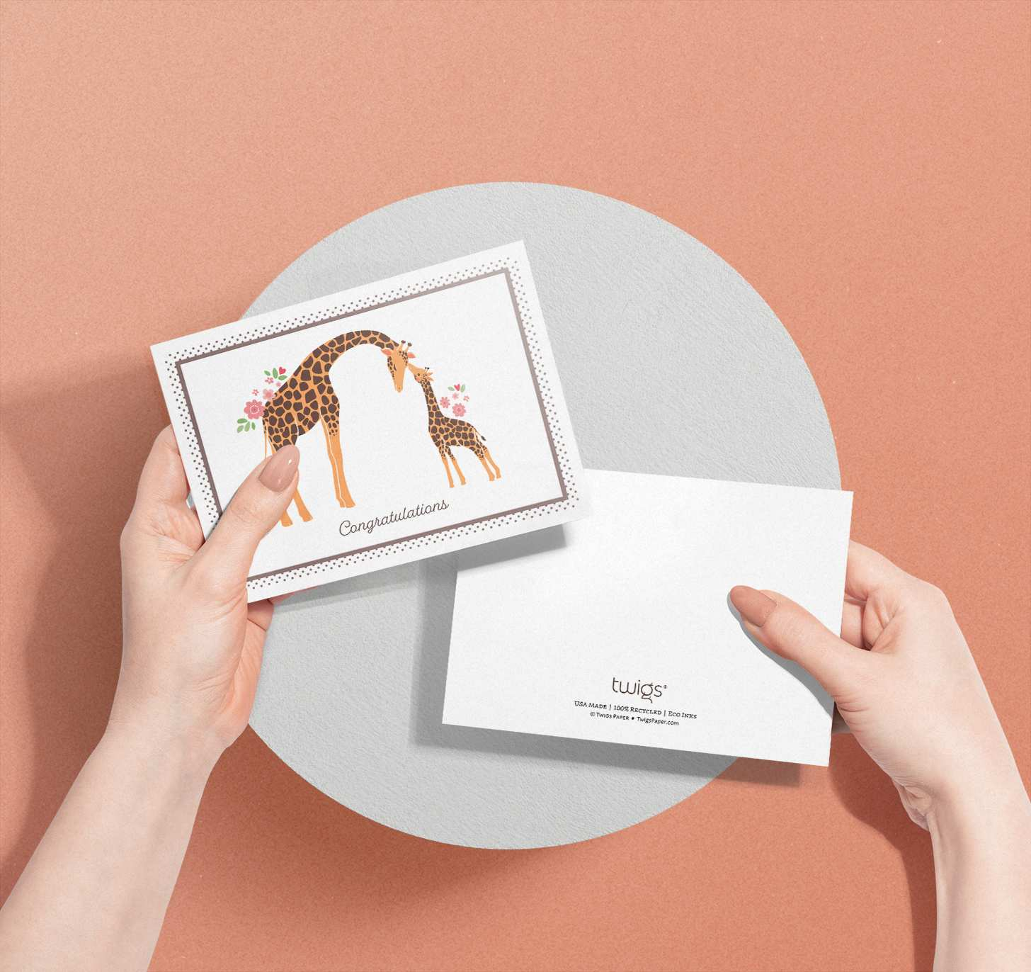 Woman's hands holding two cards with mother and baby giraffe designs