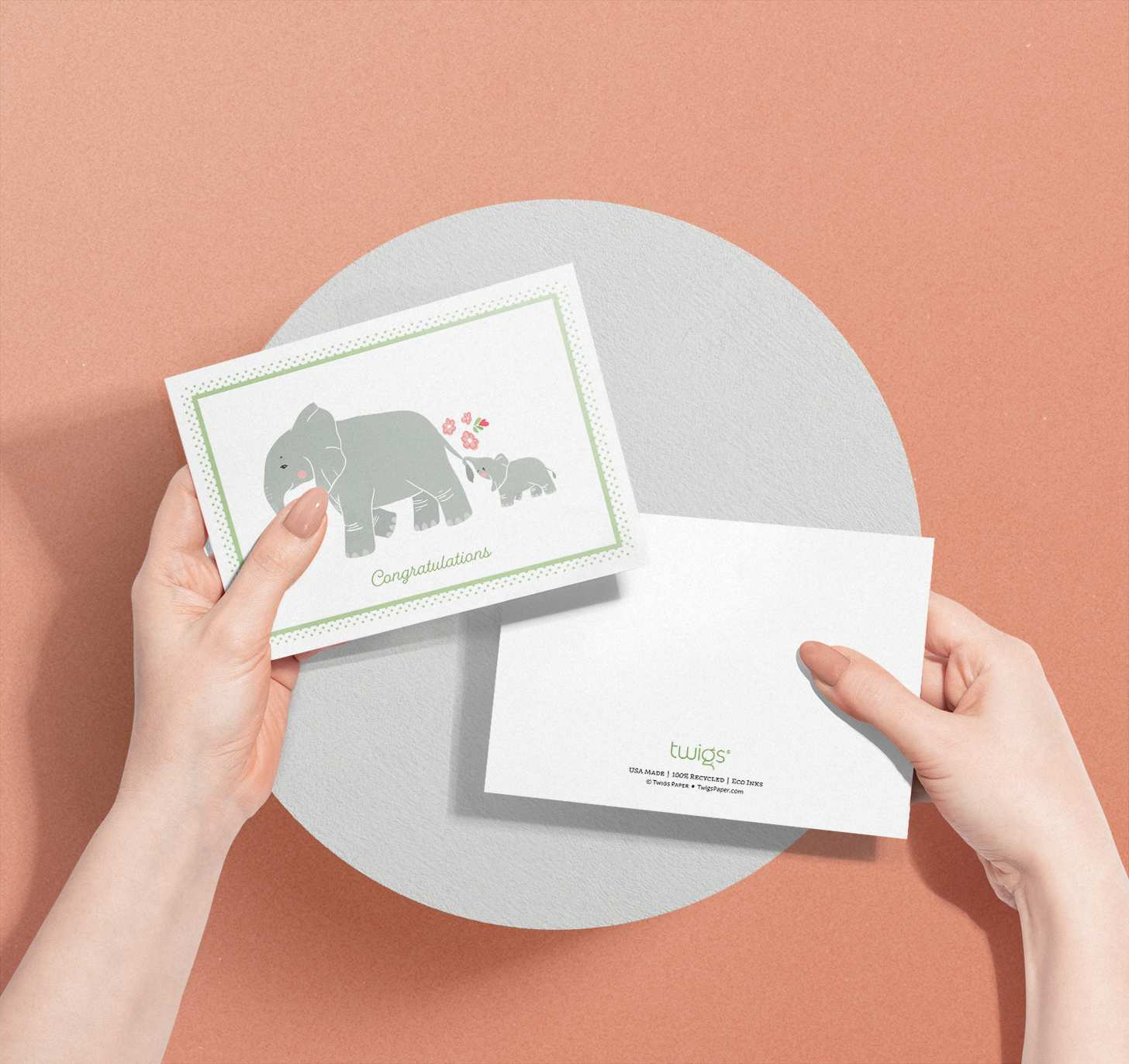 Woman's hands holding two cards with mother and baby elephant designs