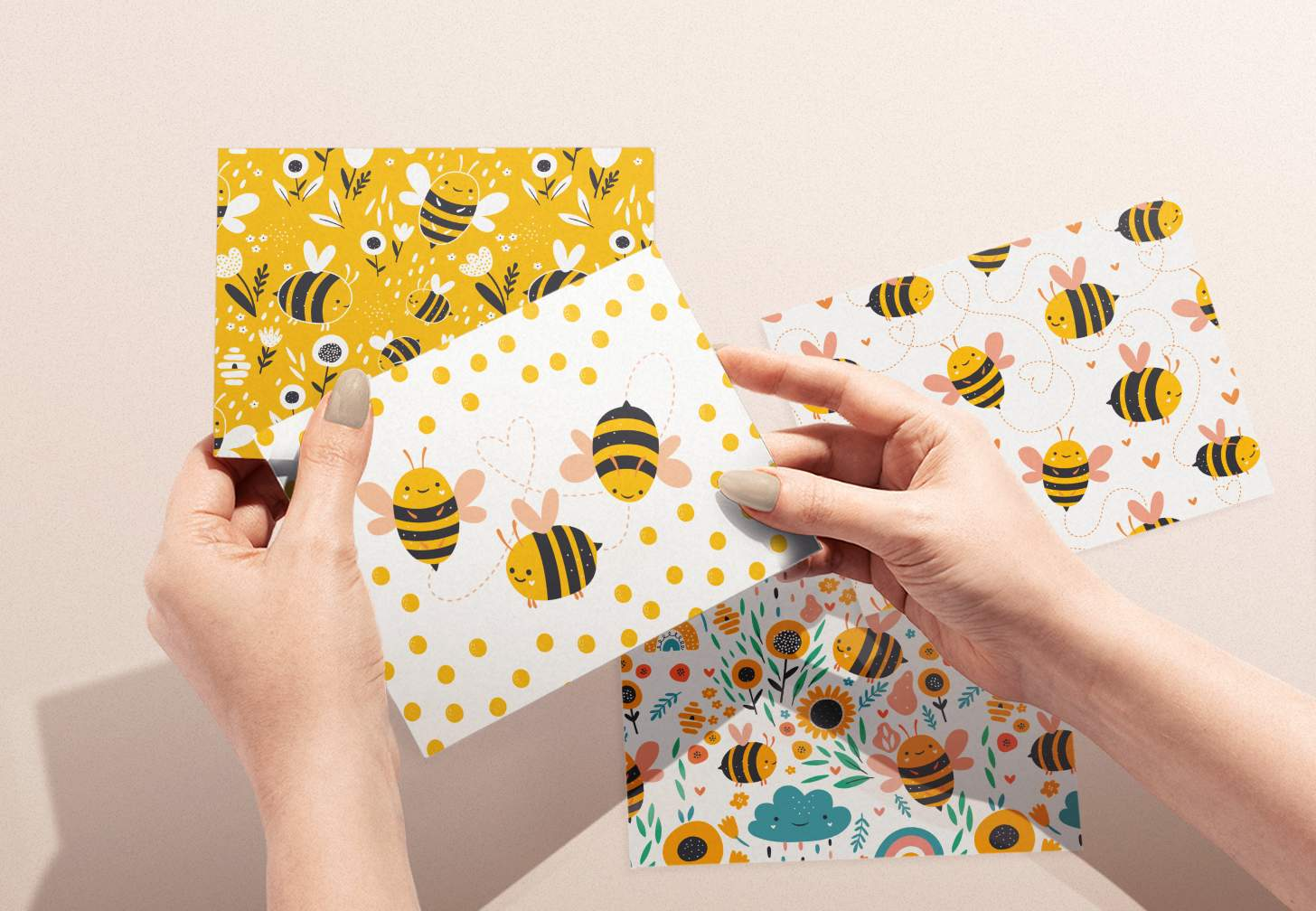 Woman's hands holding card with cute bumble bees design and assorted bumble bee cards in background