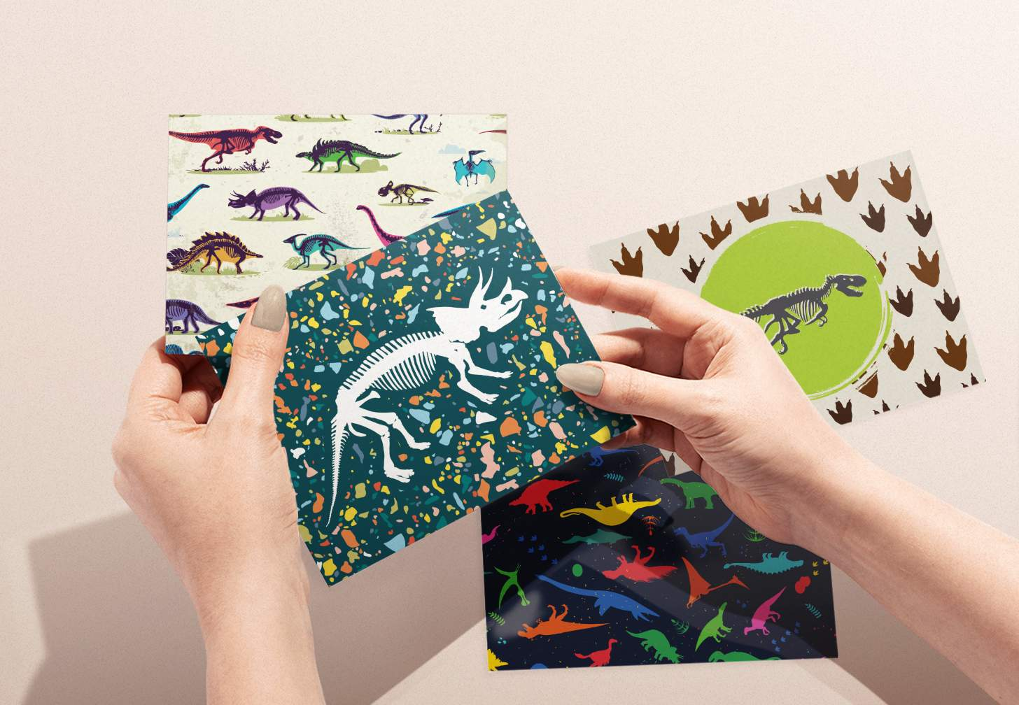 Woman's hands holding dinosaur bones design card with various dinosaur designs in background