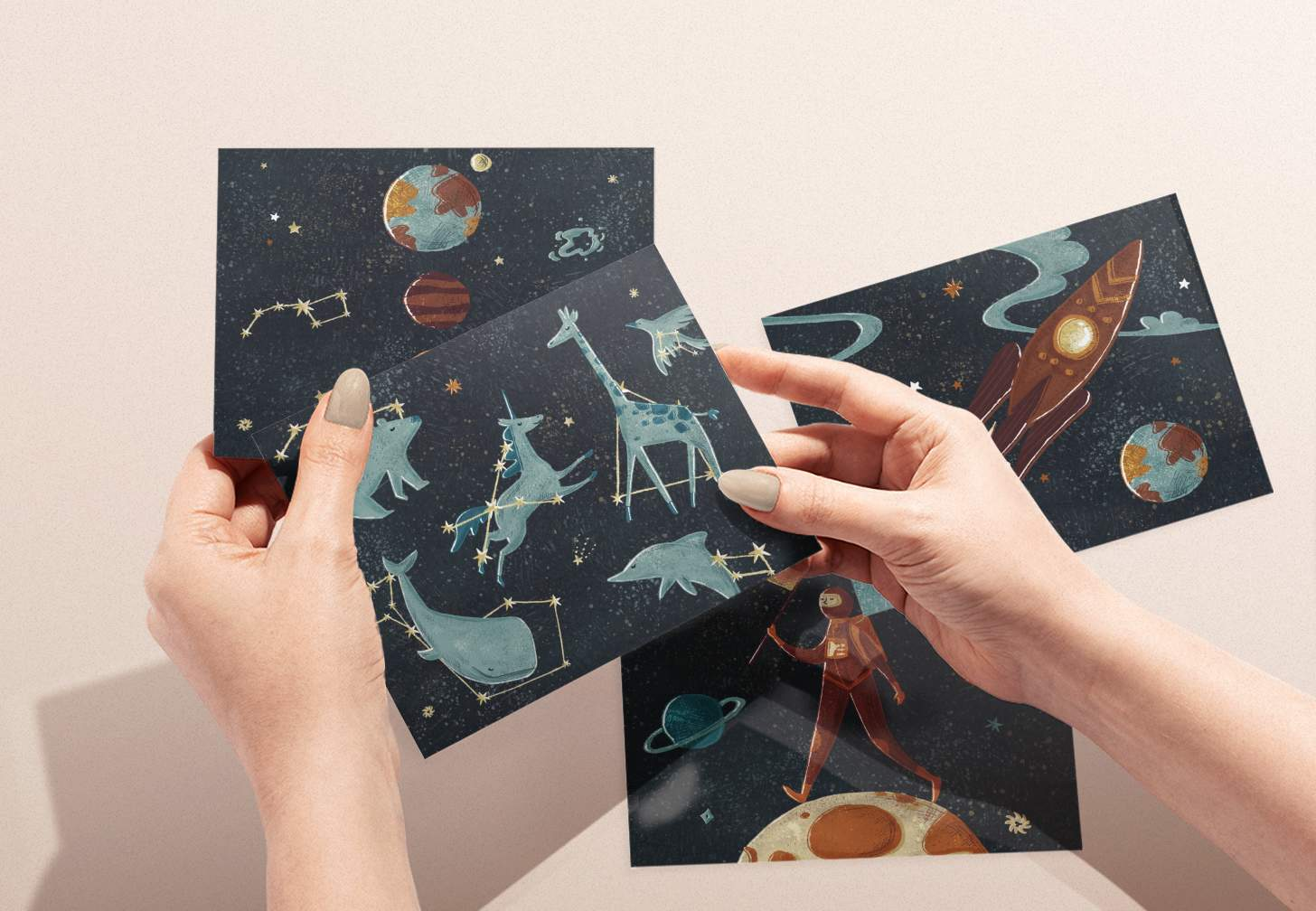 Woman's hands holding Blue animal constellation design with various outer space cards in background
