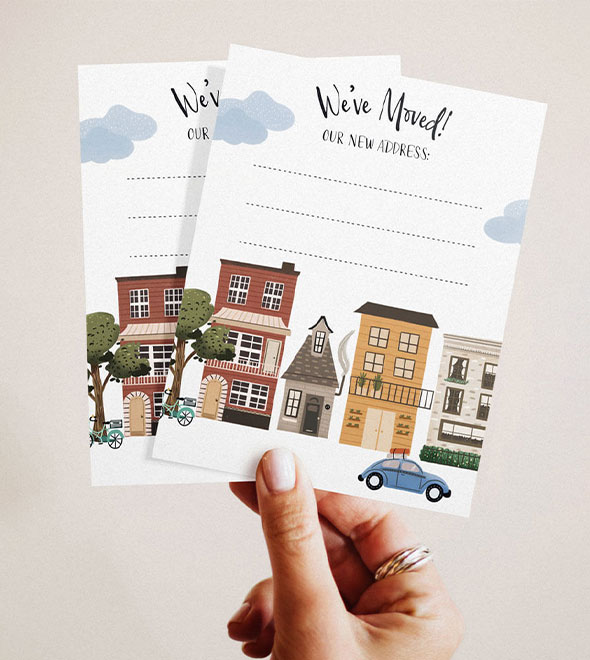 A hand holding 2 greeting cards with houses and car on it.