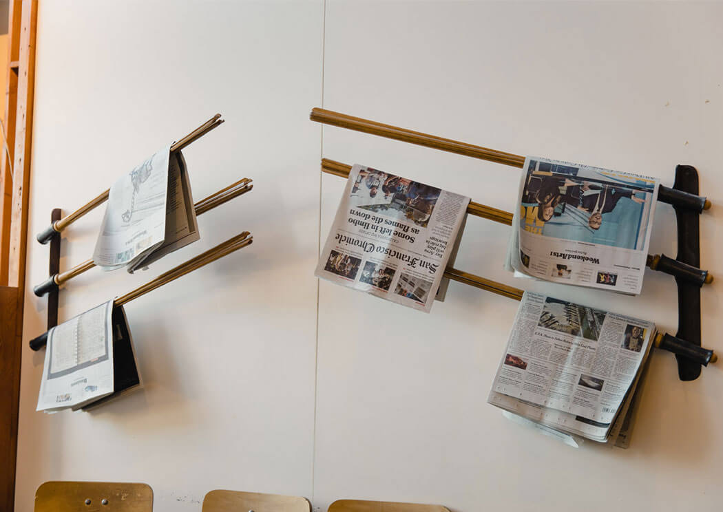 Newspapers on a rack attached on a white wall