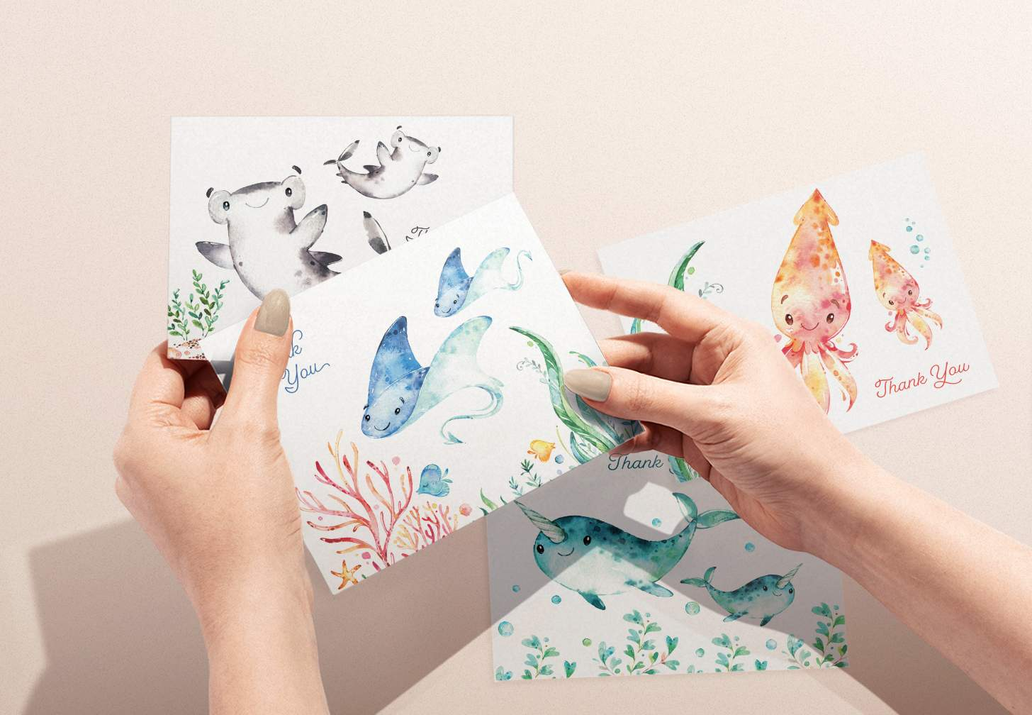 Woman's hands holding card with mother and baby sting ray design with shark, squid, and narwhal cards in background