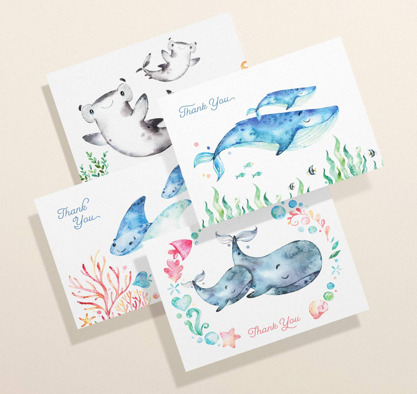 Four overlapping cards with mother and baby blue whale, gray whale, shark, and sting ray designs