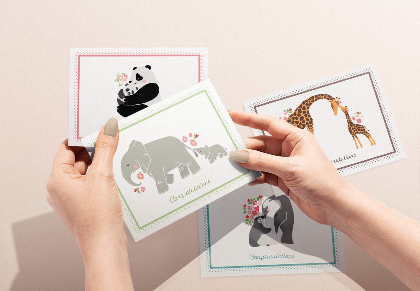 Woman's hands holding a card with mother and baby elephant design along with giraffe, panda, and penguin designs