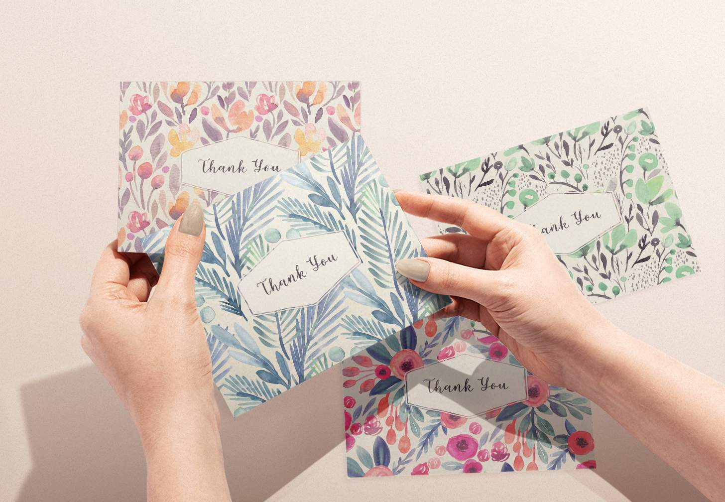 Hands holding four assorted cards with blue, green, pink, and rose color designs