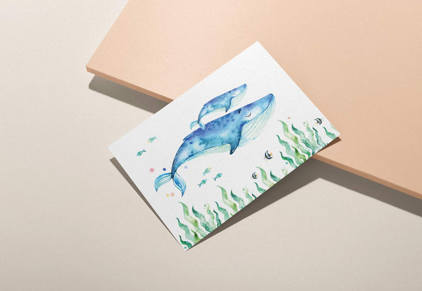 Mother and baby blue whale design with tropical fish on a pink background