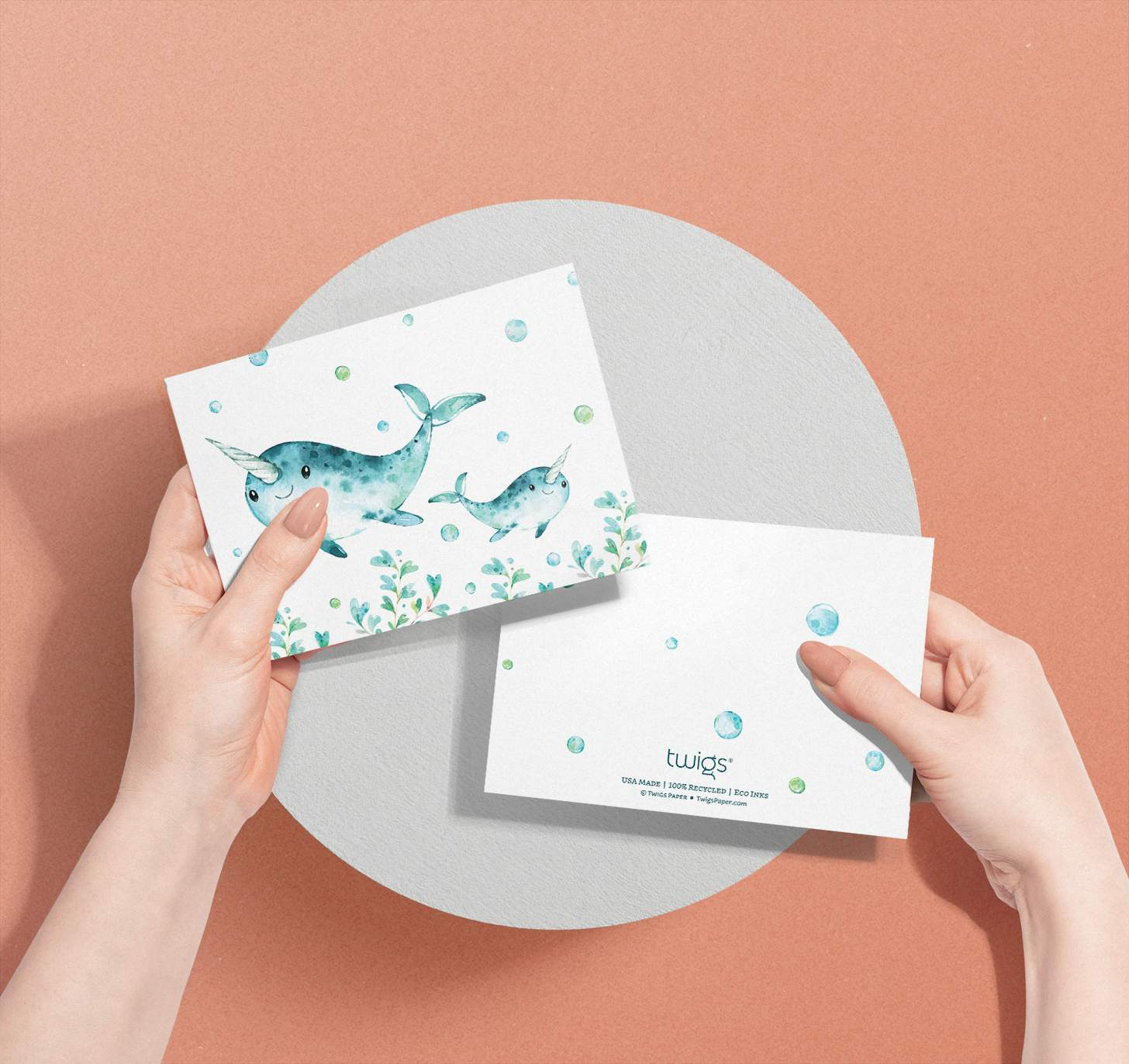 Woman's hands holding Mother and baby narwhal cards with bubbles