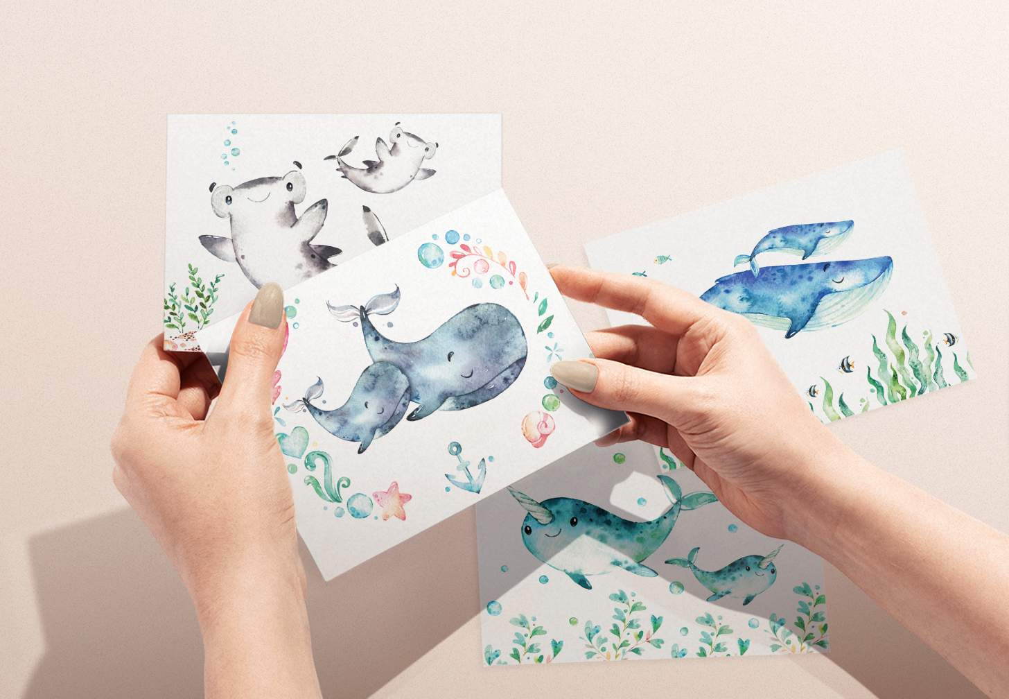 Woman's hands holding card with mother and baby gray whale design with shark, blue whale, and narwhal in background