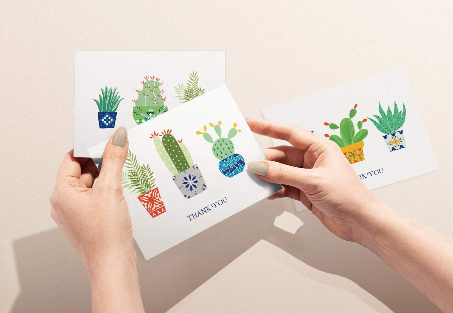 Hands holding colorful succulents design card with various cactus cards in background