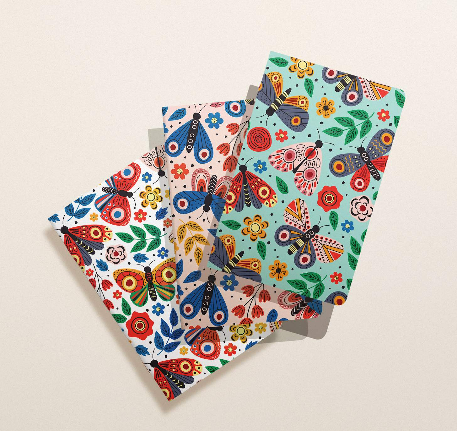 Three assorted overlapping blue, white, and pink colorful butterfly notebooks
