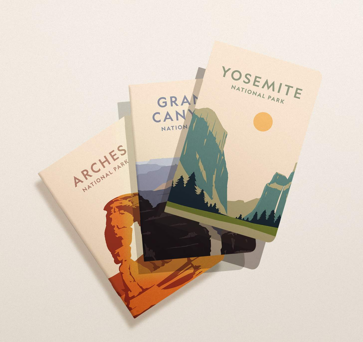 Three overlapping assorted Arches, Yosemite, and Grand Canyon national park notebooks