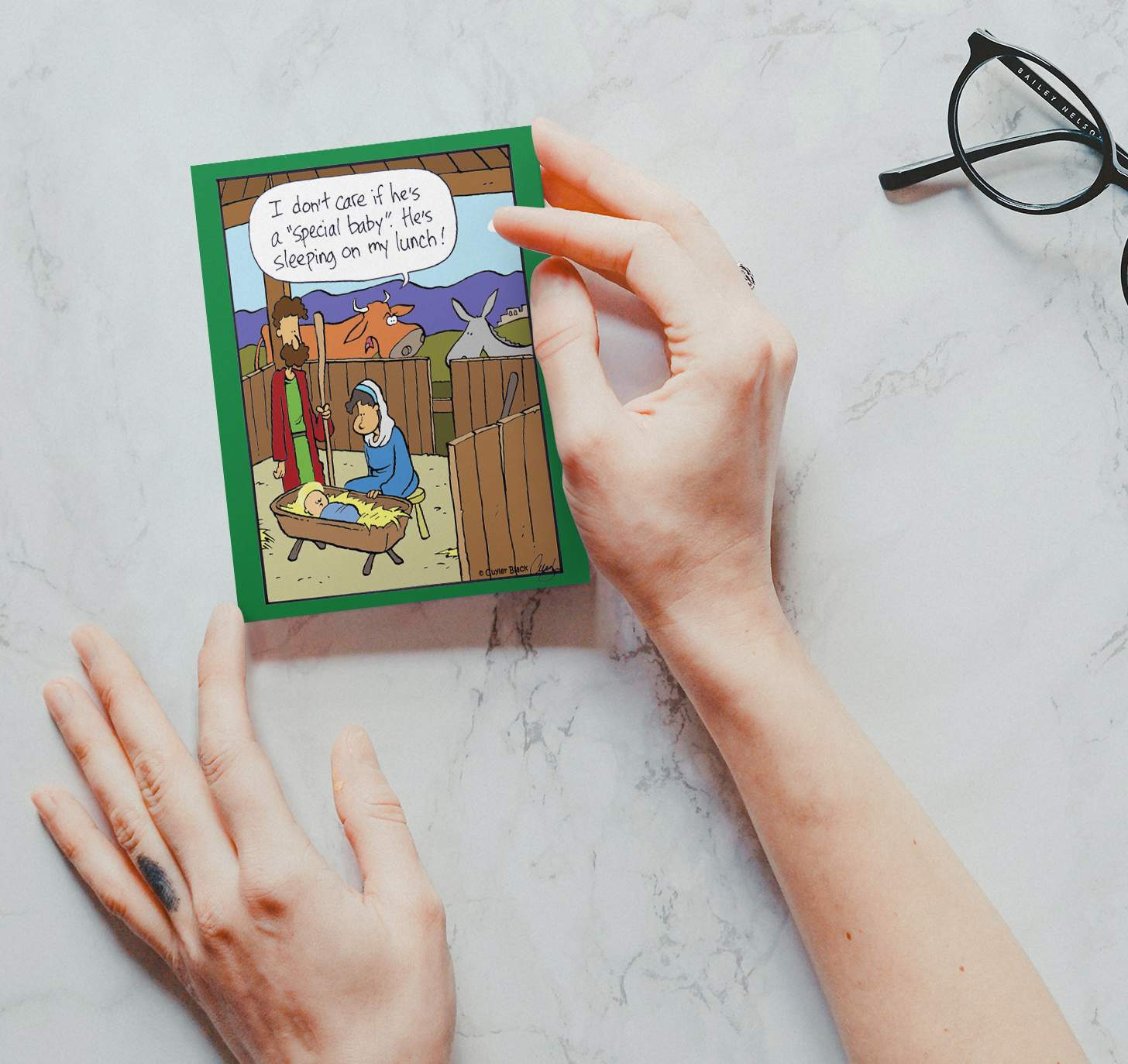Hands holding card with baby Jesus on marble background
