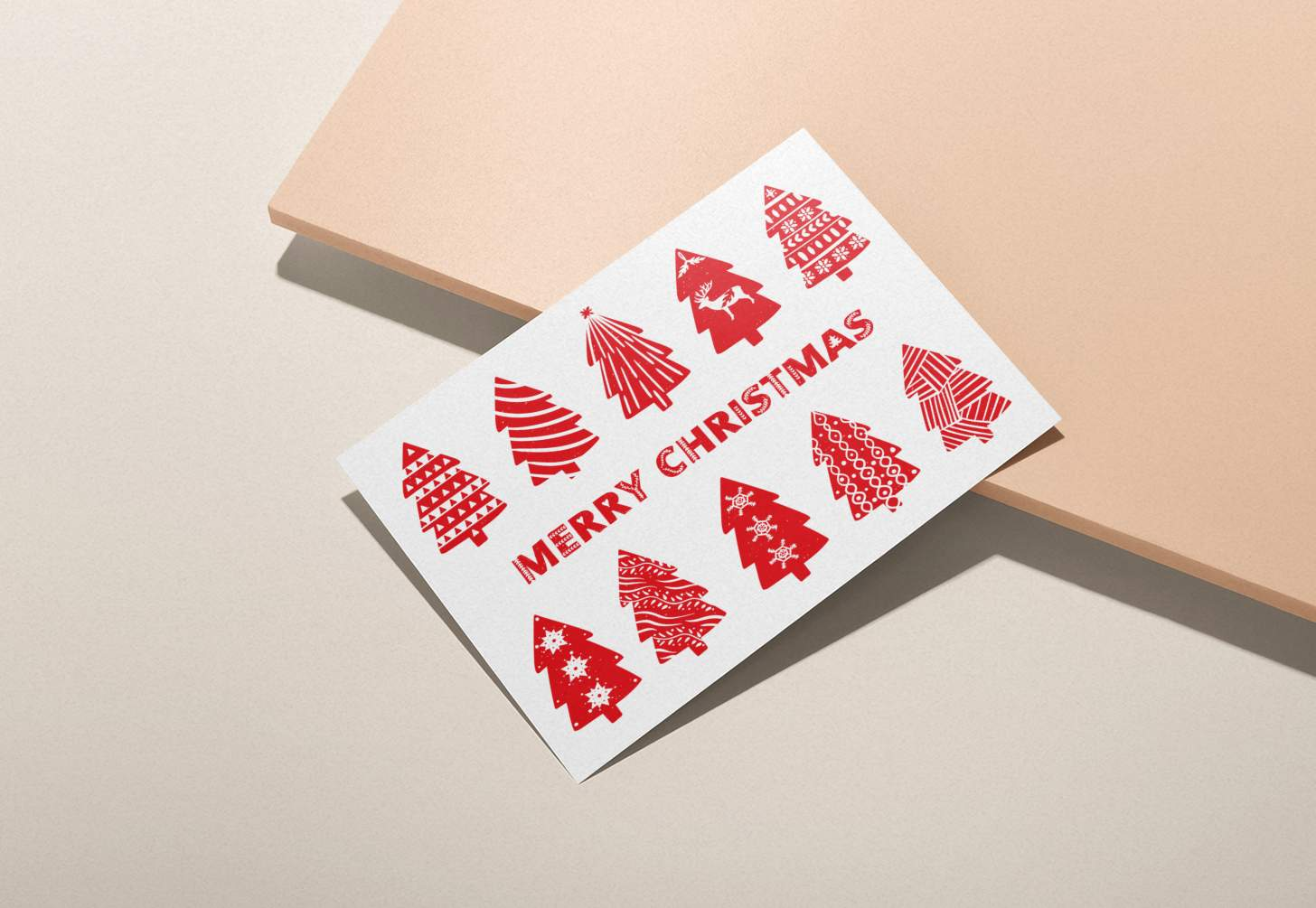 Hands holding red and white Merry Christmas with Christmas trees design on pink background