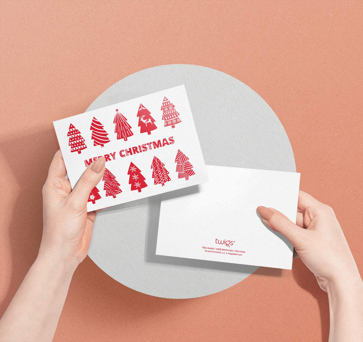 Hands holding red and white Merry Christmas with Christmas trees design