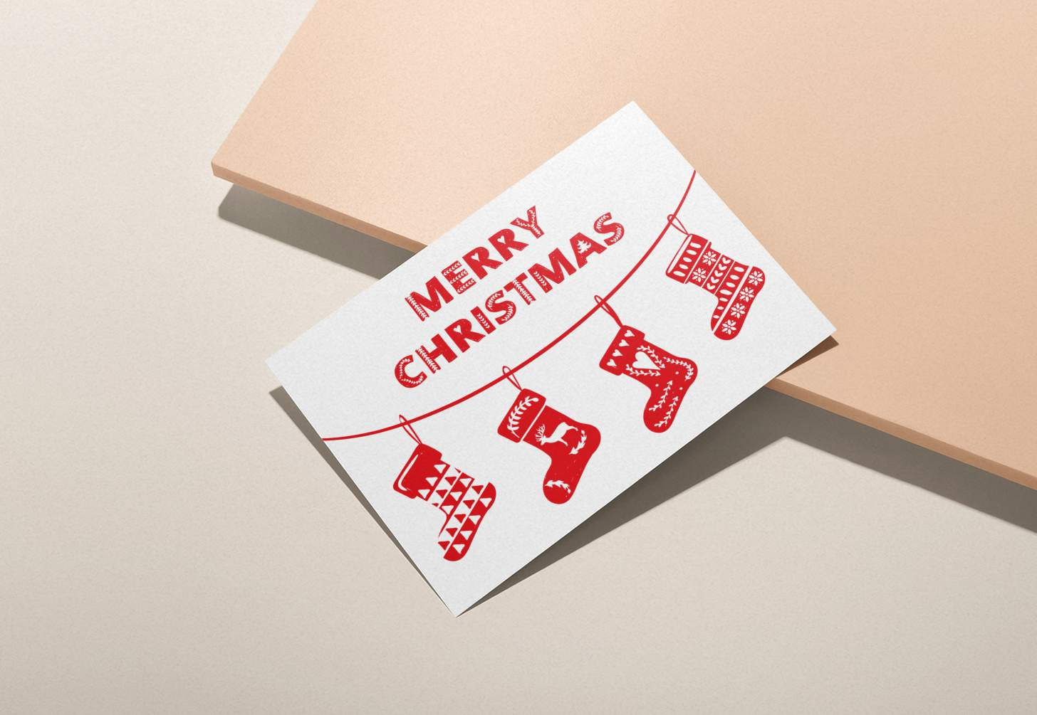 Hands holding red and white Merry Christmas with stockings design on pink background
