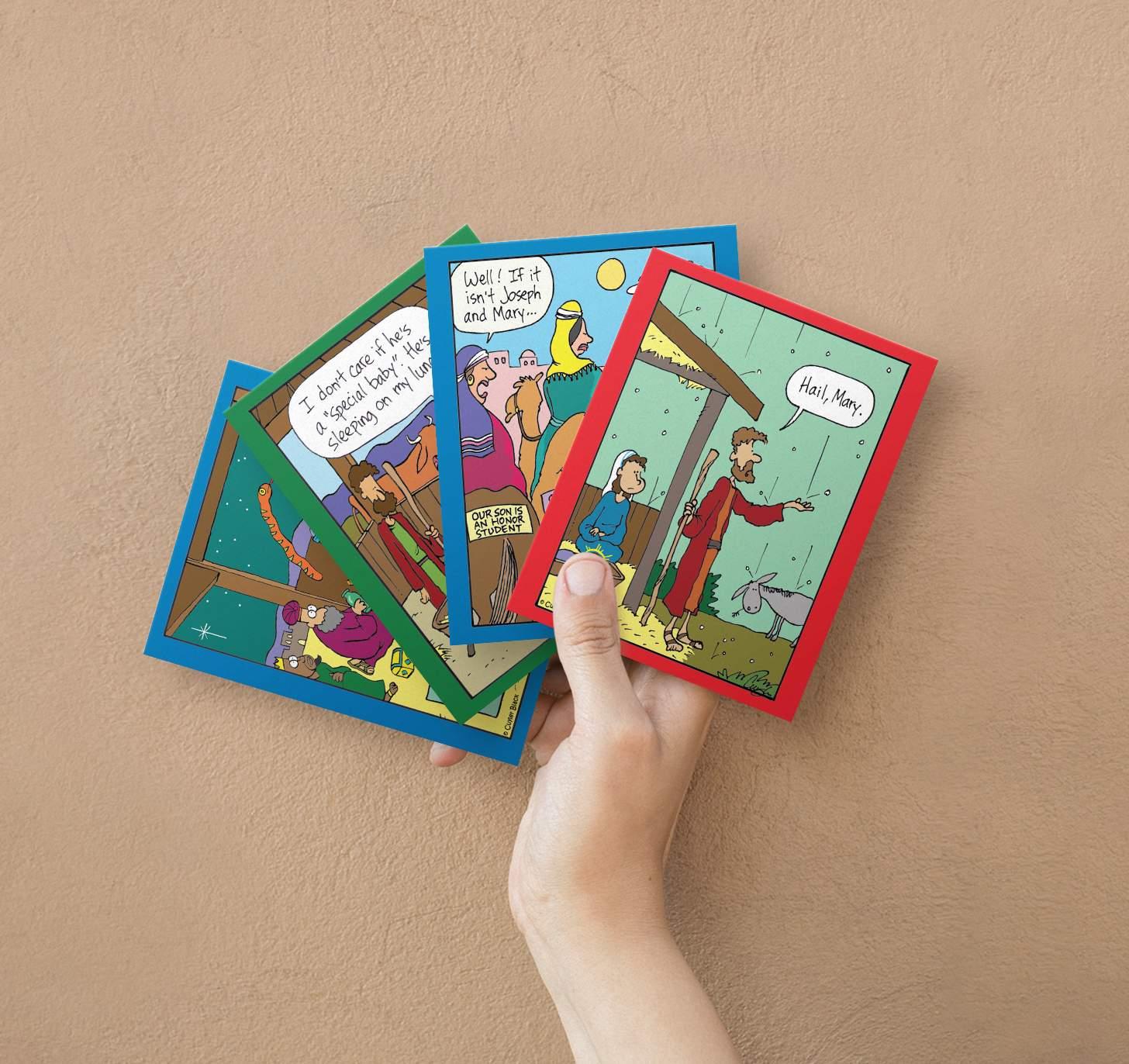 Hands holding assortment four funny religious Christmas cards