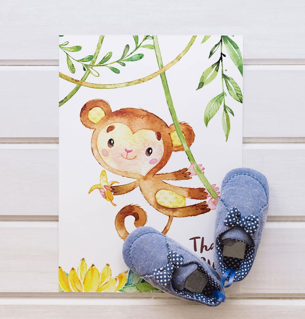 Blue baby shoes placed on top of a greeting card with cute baby monkey
