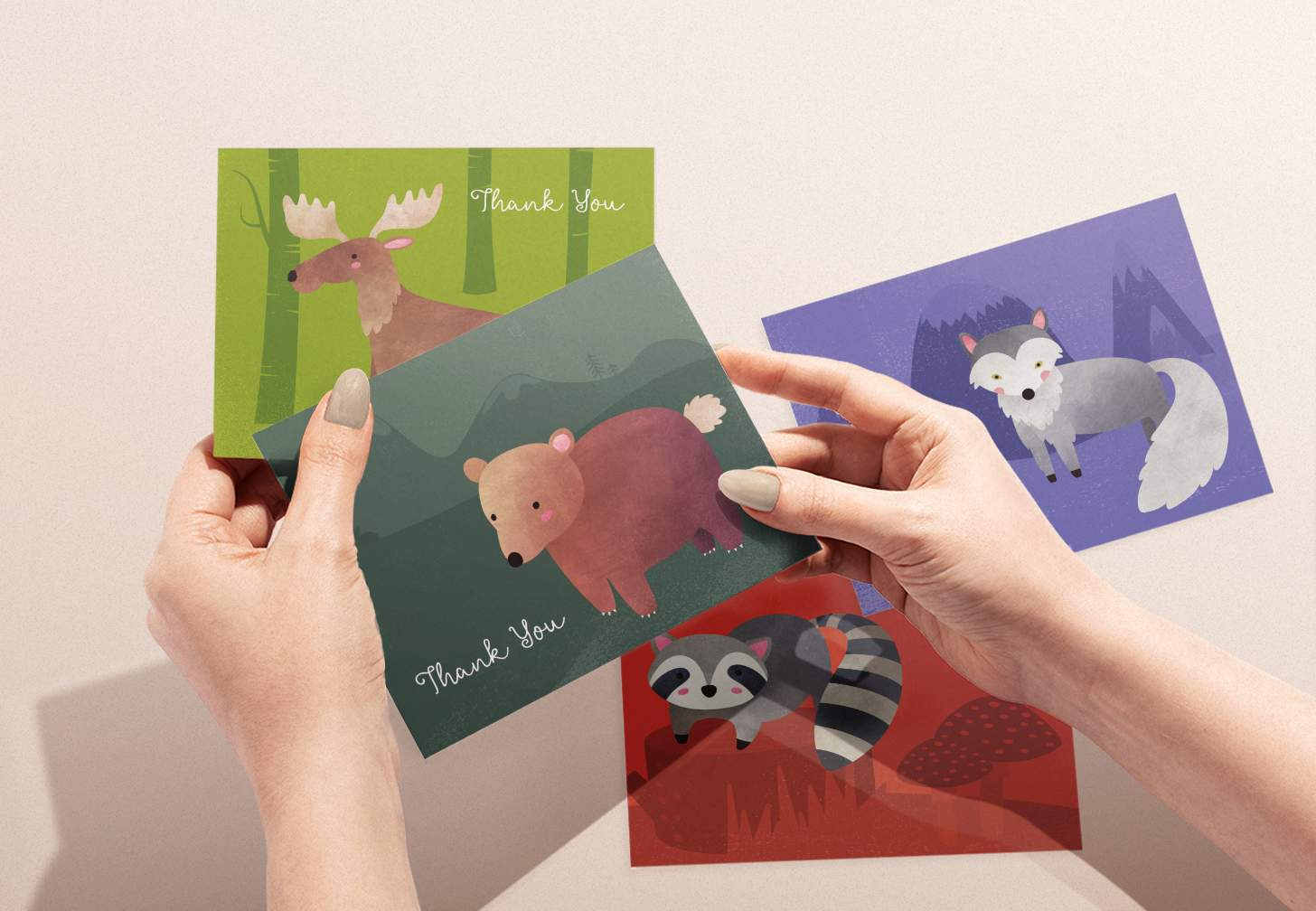 Woman's hands holding card with cute brown bear design with moose, raccoon, and wolf designs in background