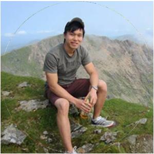 Jon L sitting on a rock looking happy