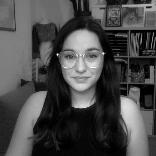 A black and white image of Meri sitting at her desk in her home office, wearing glasses with her dark hair down, smiling into the camera.