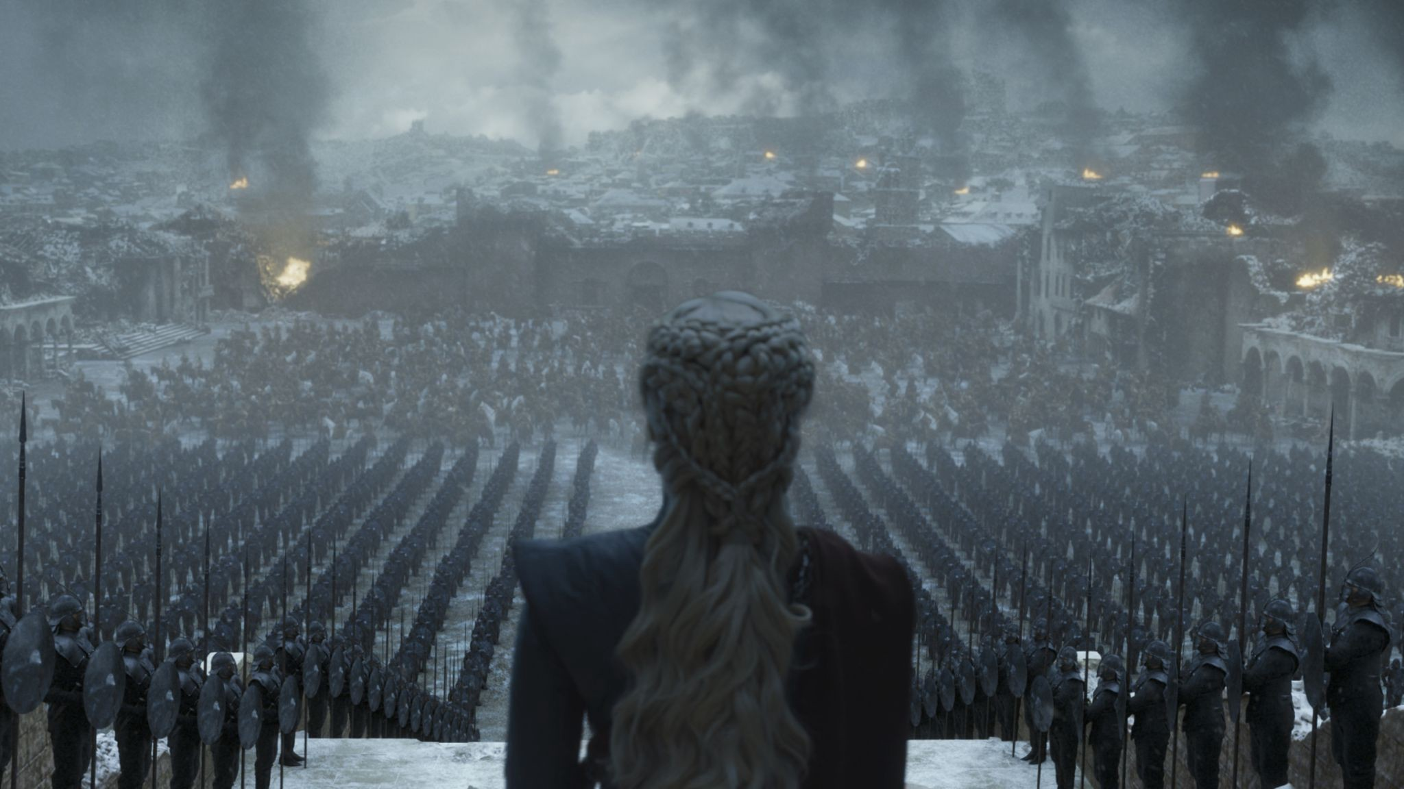 An image from HBO's Game of Thrones. Daenerys Targaryen watches over her troops. They stand in formation, ahead of a battlefield.