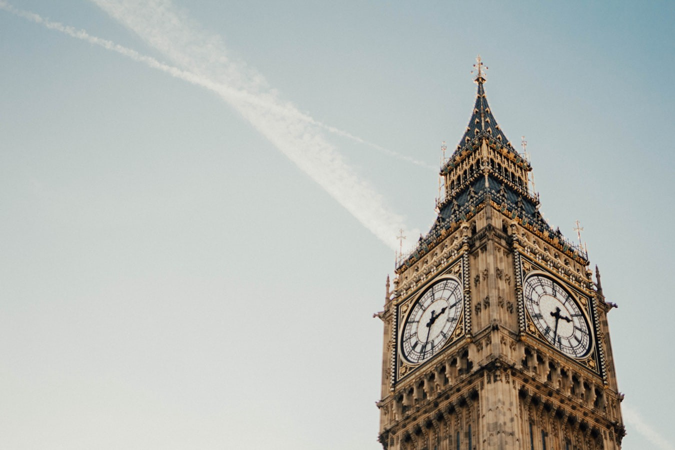 A picture of Big Ben's clock, with vapor trails in the sky behind.