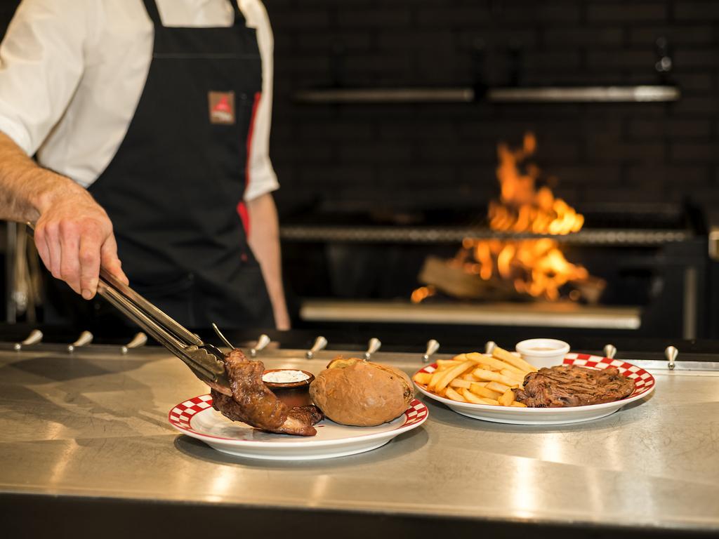 Employé en train de faire cuire un steak chez Courtepaille