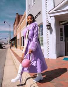 Fashionable woman in purple coat walking on a street