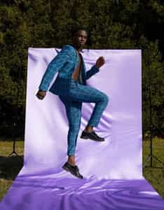 Man jumping in front of backdrop wearing a suit