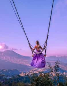 Woman on a swing during sunset in purple dress
