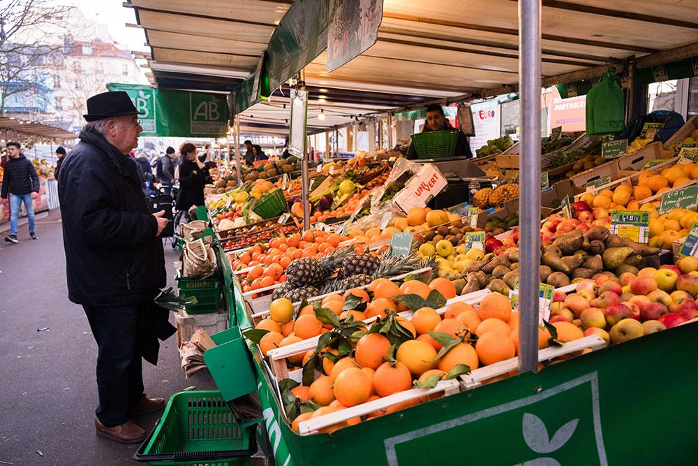 Wochenmärkte in Essen Mann mit Hut steht vor Stand mit Obst und Gemüse