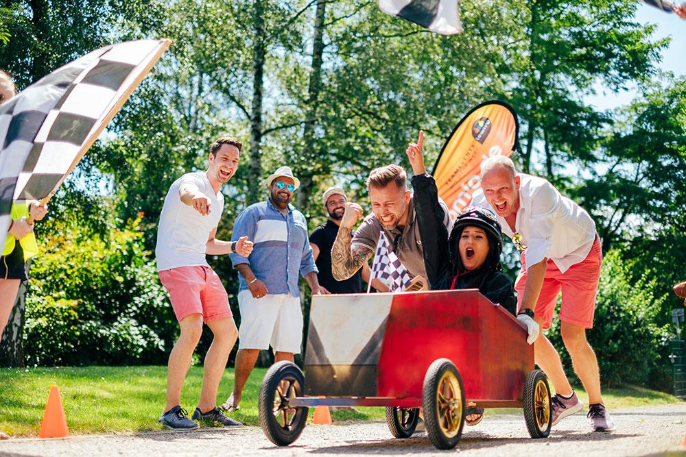 Junge Leute feuern Fahrer in selbstgebauter Seifenkiste an