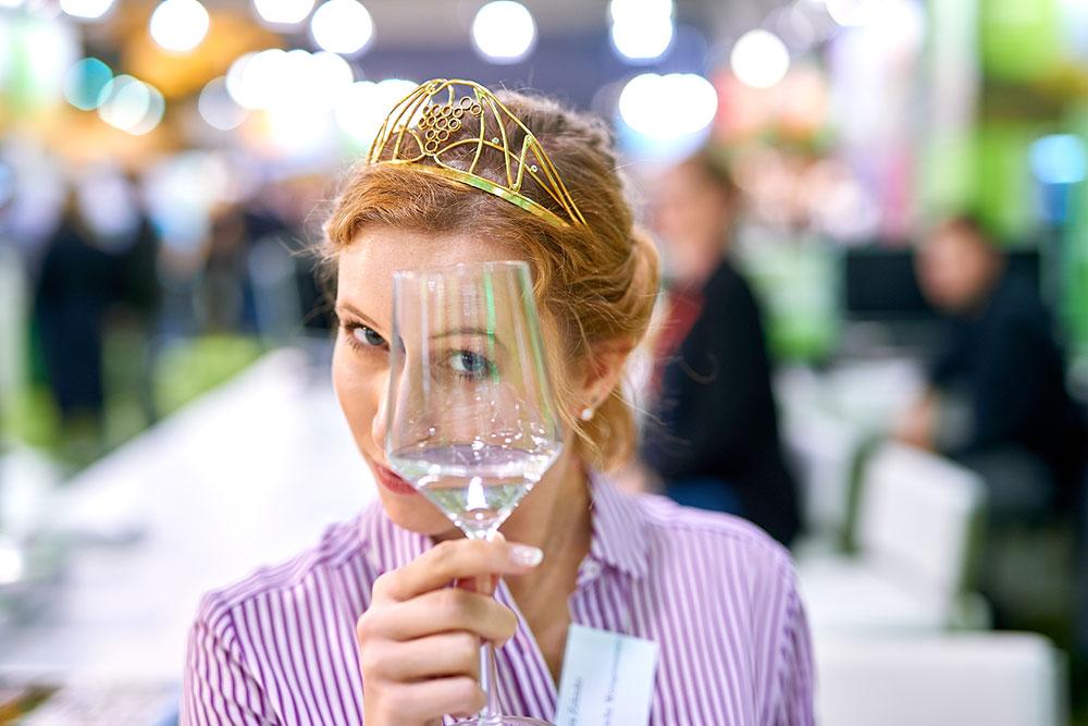 Die DeutscWeinprinzessin mit Krone und Weinglas vor der Kamera he Weinprinzessin bei der WeinTour.