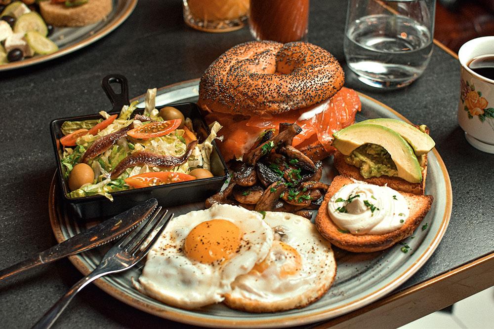 Spiegelei, Avocado und geräucherter Lachs im Bagel serviert zum Frühstück