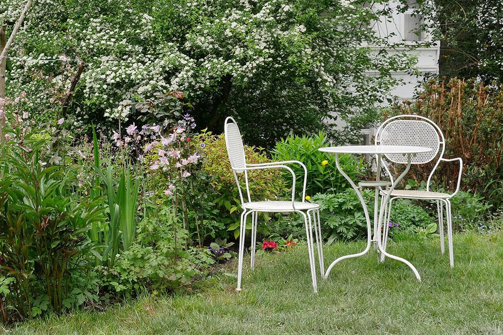 Weisse Gartenmöbel im barocken Stil in idyllischer Gartenanlage