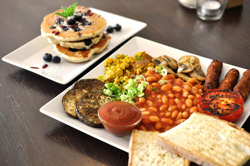 Veganes englisches Fühstück mit Pancakes auf weißen Tellern