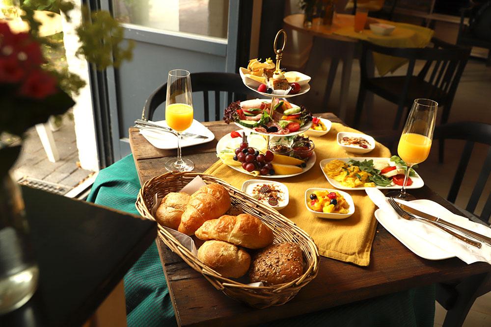 Frühstück mit hausgemachten Granola, Joghurt mit frischen Früchten und Brötchen, die mit Frühlingsfrischkäse, frischem Gemüse & Beeren belegt sind