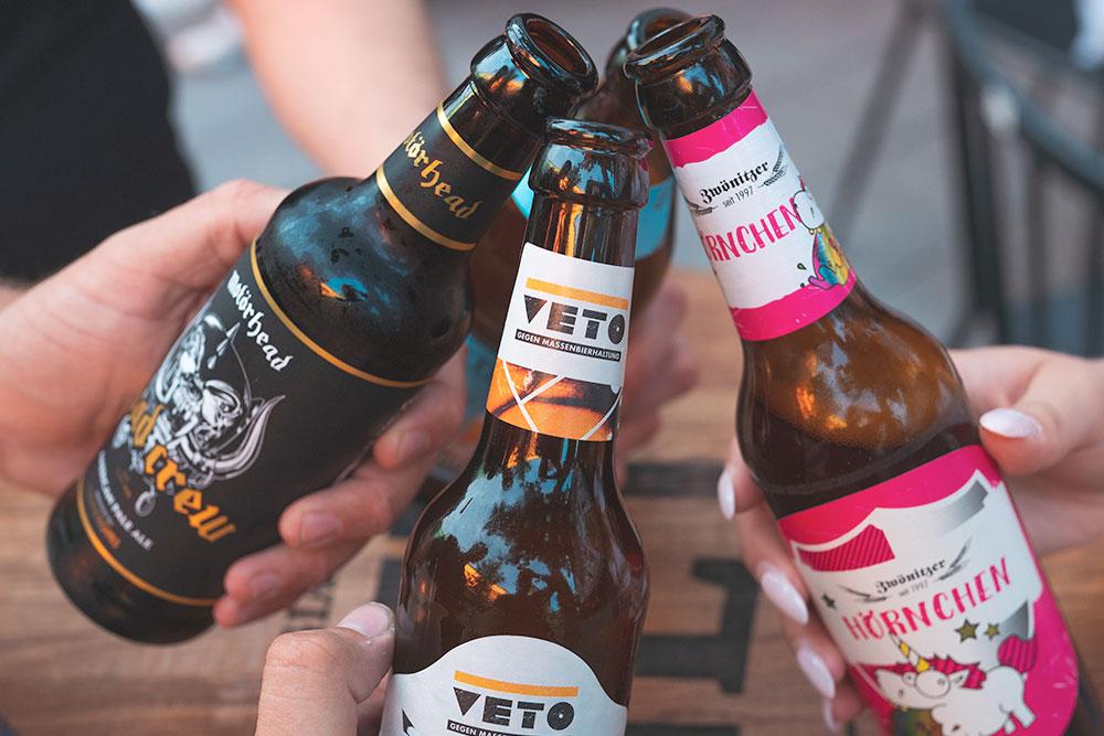 Drei Flaschen Bier mit haende bei der neuen Bierbar Miss Hops in Ruettenscheid