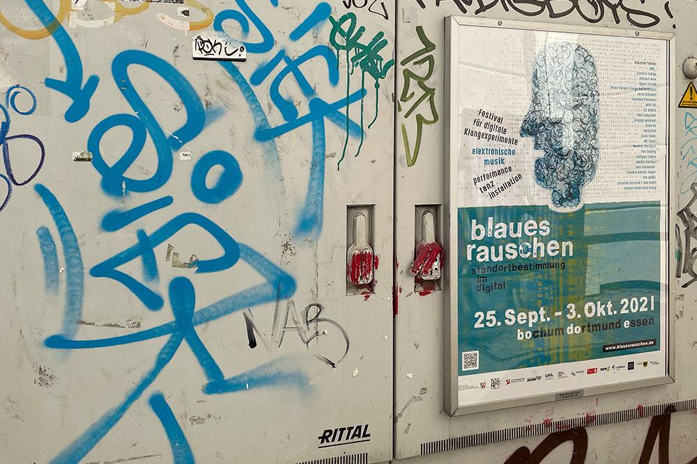 Blaues Rauschen Plakat auf Stromkasten mit Grafitti
