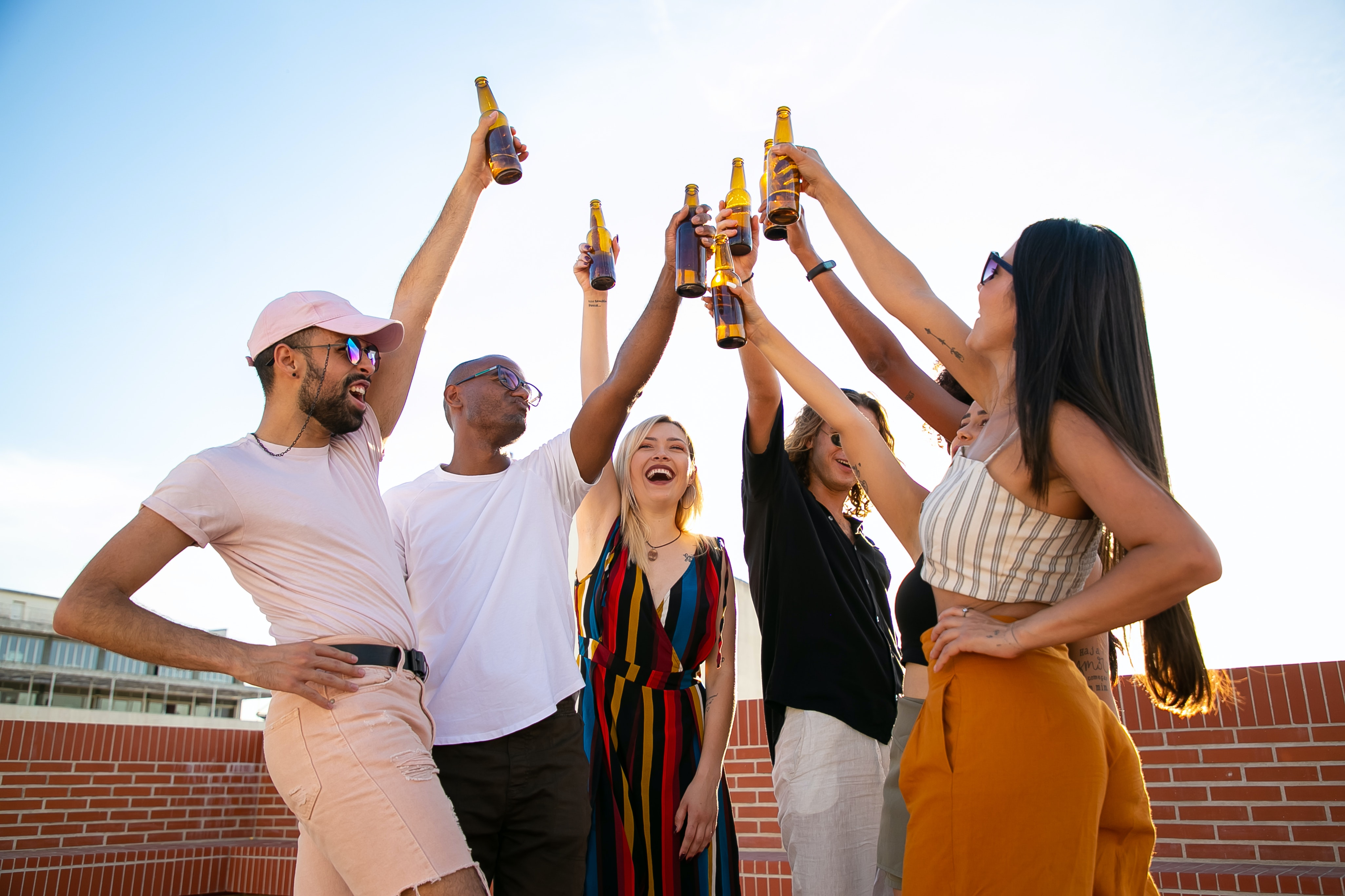 Celebrating people raising up their bottles with drinks