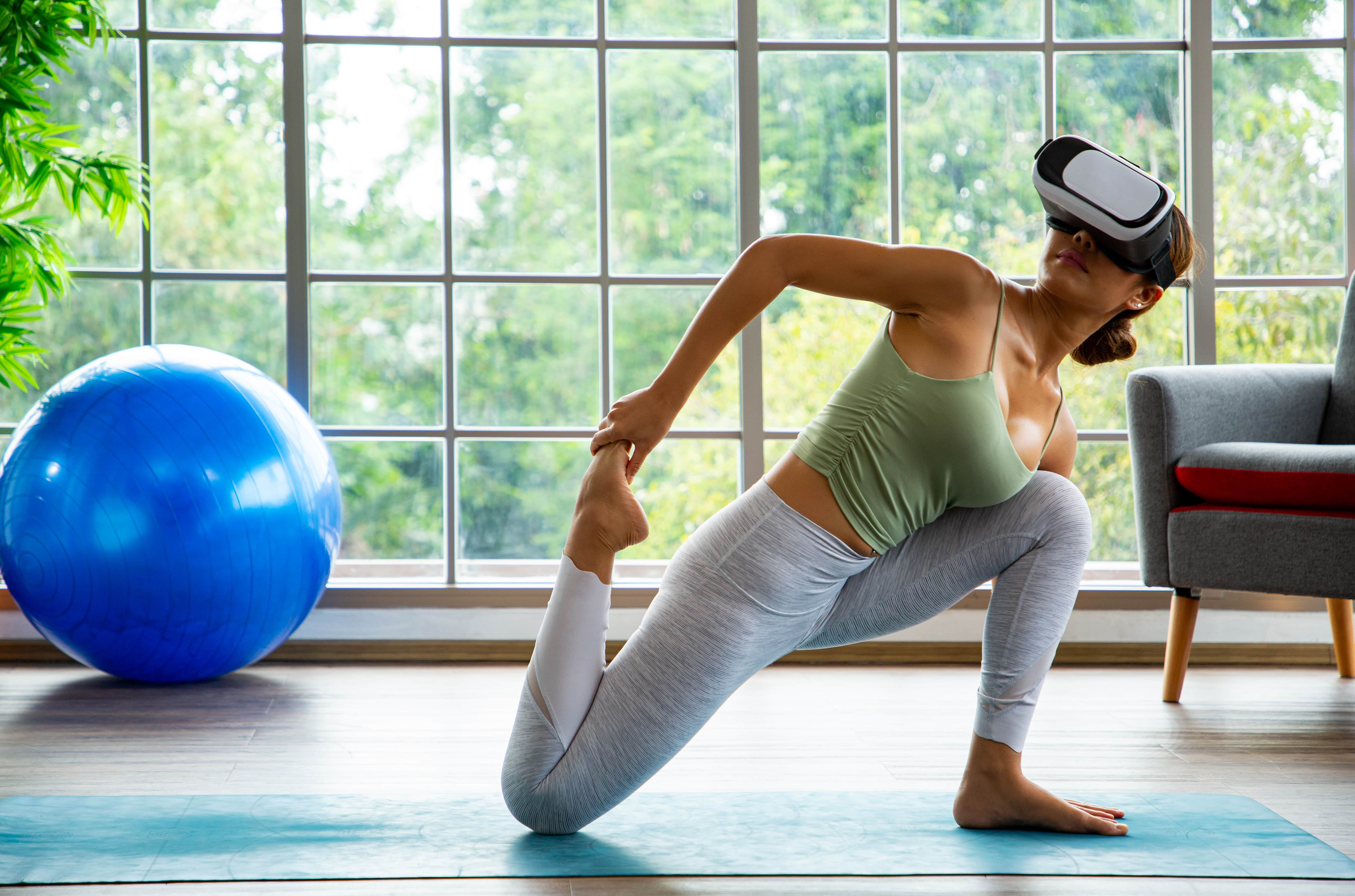 Healthy asian woman relaxing zen with virtual reality sitting on mat and conect outside VR headset glass device.People and technology concept stay at home.