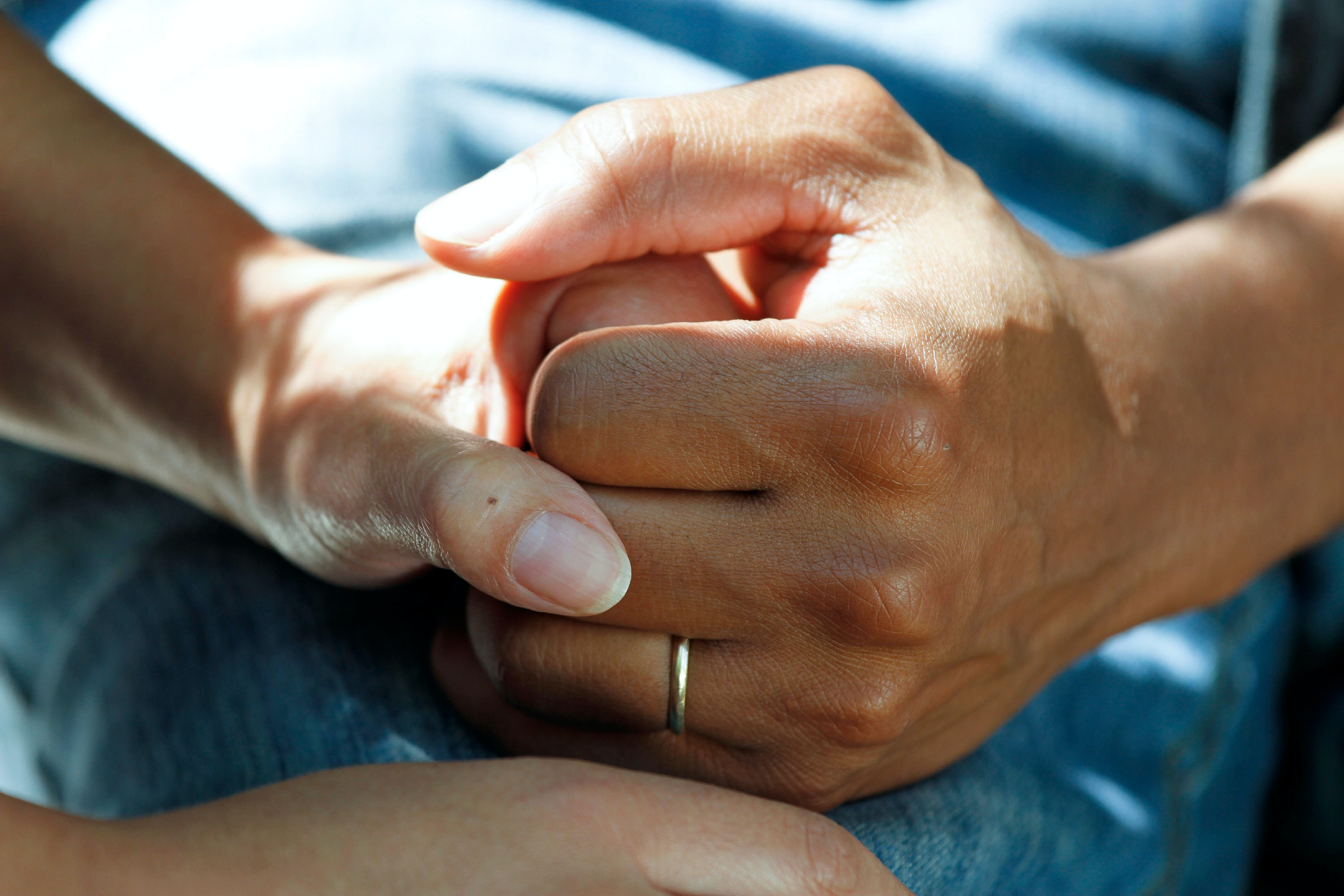 two companion hands holding each other for support