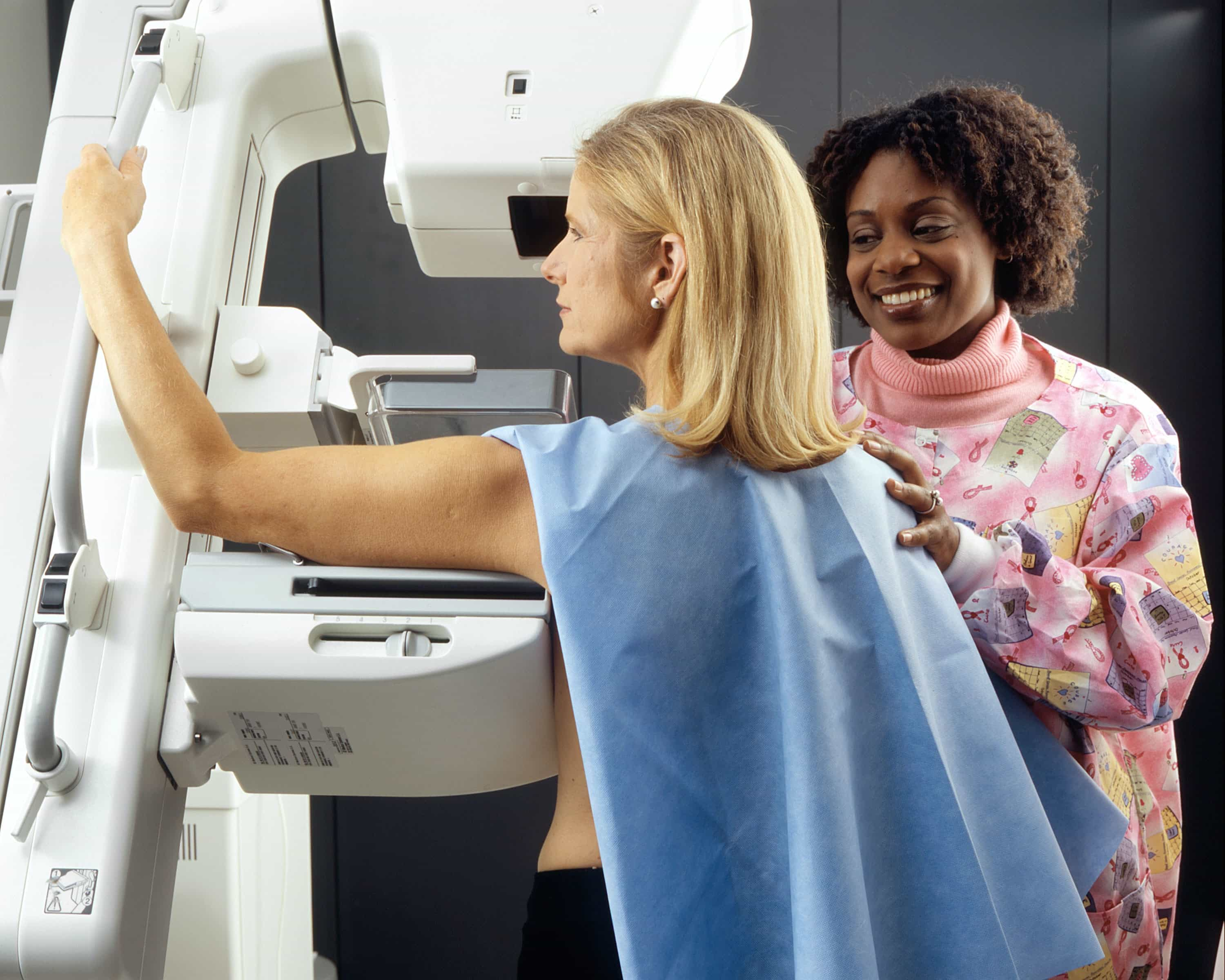a woman having a mammogram screening being supported by a nurse