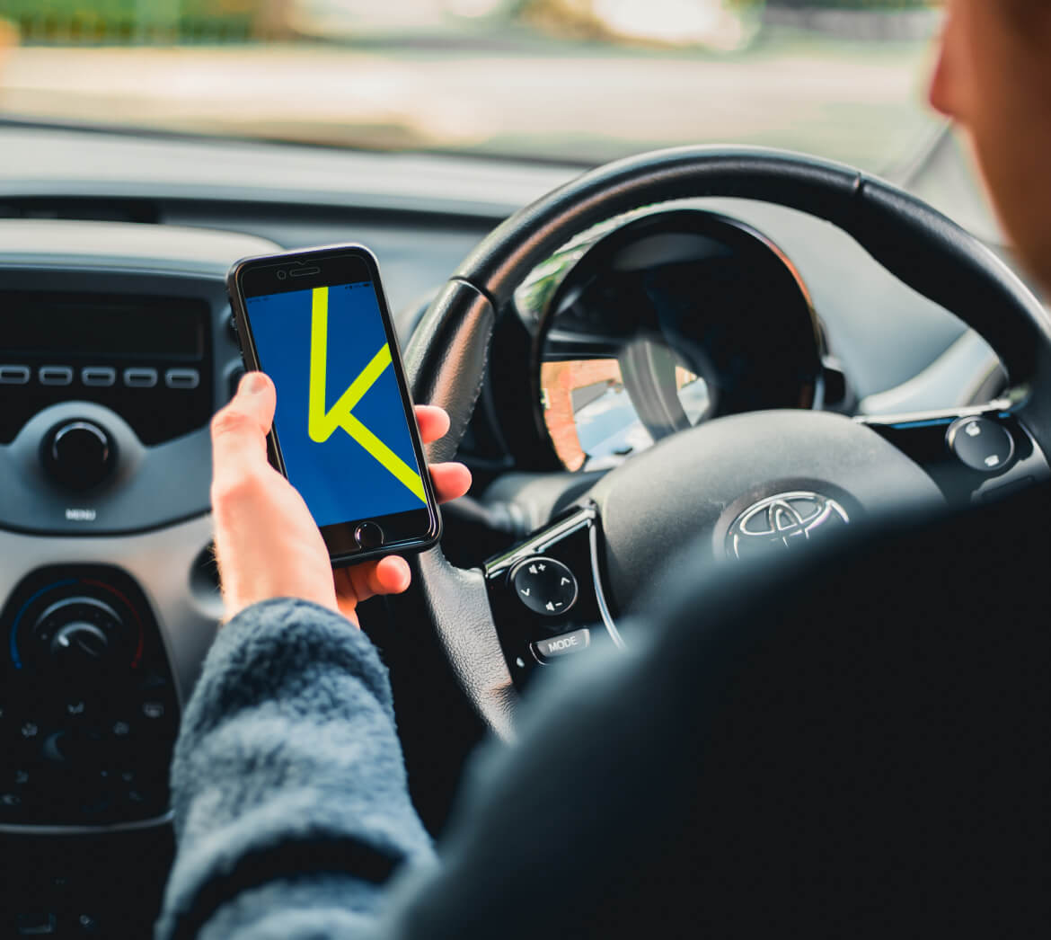Karshare App next to steering wheel for car rentals and car sharing